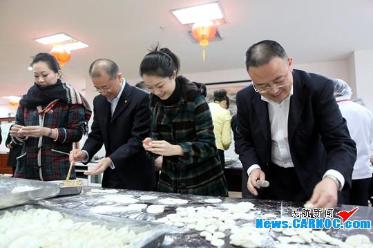 图:深航党委书记樊澄,总裁助理王爱武与员工一起包饺子 摄影:邓冠群