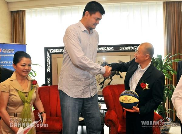 图4:国航党委书记樊澄接受姚明赠送的姚基金希望小学的篮球.